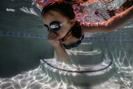 Girl closing nose wearing goggles while swimming in pool - CAVF62606