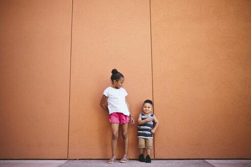 Full length of siblings standing on footpath against orange wall - CAVF62615