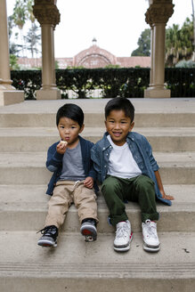 Portrait of cute brothers sitting on steps against sky at Balboa Park - CAVF62642