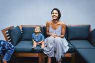 Portrait of happy mother with cute daughter sitting on sofa against wall at home - CAVF62678