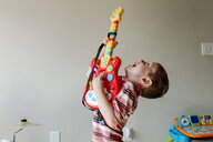 Cute happy boy singing while playing toy guitar against wall at home - CAVF62705