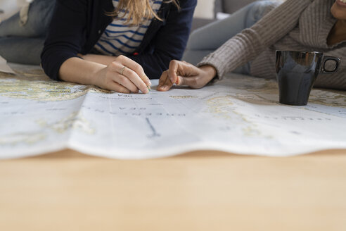 Friends putting pins on a map, planning their vacations, close up - FMOF00421