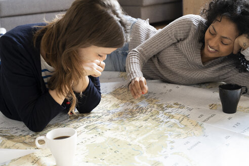 Friends putting pins on a map, planning their vacations - FMOF00424
