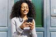 Laughing woman holding smartphone - FMOF00439