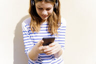 Young woman sith geadphones using smartphone - FMOF00448