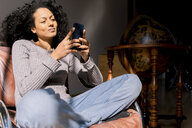Woman sitting relaxed in armchair, using smartphone - FMOF00451