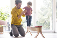 Father helping his daughter to balance on a beam - JOSF03082