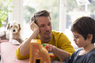 Father and son playing with a toy till - JOSF03088