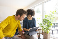 Couple sitting in living room, using digital tablet - JOSF03097