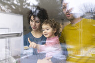 Family looking out of window, mother carrying daughter, pointing - JOSF03103