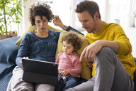 Family lying on couch watching movie on theit tablet - JOSF03109