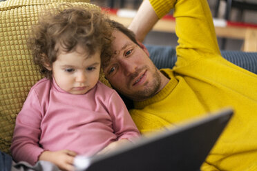 Father and daughter lying on couch watching movie on theit tablet - JOSF03112