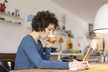 Young woman sitting at table, using digital tablet, drinking coffee - JOSF03118