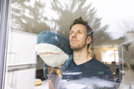 Man looking out of window, carrying toy shark on his shoulder - JOSF03121