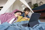 Mother and son lying in play tent, watching movie on tablet - JOSF03124