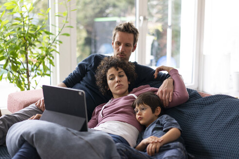 Family lying on couch watching movie on theit tablet - JOSF03133