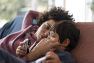 Family cuddling on couch - JOSF03136