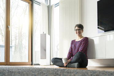 Portrait of laughing woman sitting on the floor of living room - SBOF01826