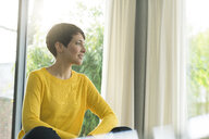 Woman sitting in the living room  looking out of window - SBOF01835