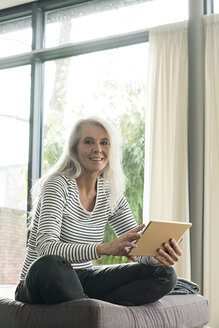 Portrait of happy mature woman using digital tablet at home - SBOF01838
