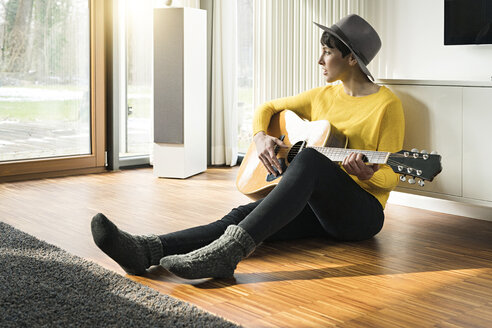 Woman sitting on the floor of living room playing guitar - SBOF01841