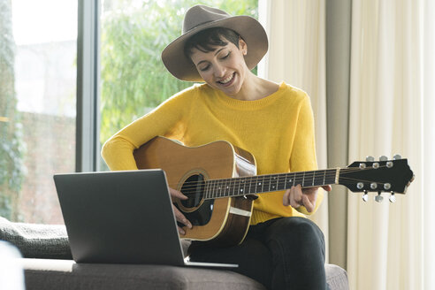 Portrait of smiling woman sitting on couch with laptop playing guitar - SBOF01844