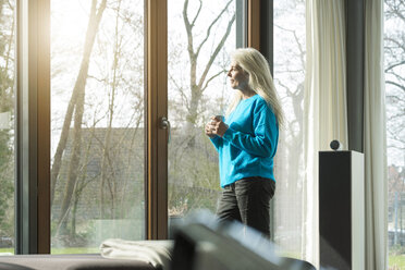 Content mature woman with cup of coffee leaning against terrace door looking at distance - SBOF01850