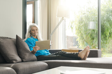 Portrait of content mature woman sitting on the couch at home looking at digital tablet - SBOF01856