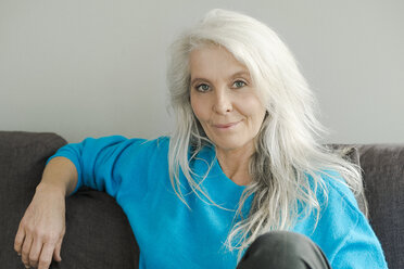 Portrait of smiling mature woman sitting on the couch at home - SBOF01859