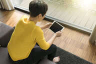 Woman sitting on couch in the living room looking at digital tablet - SBOF01868