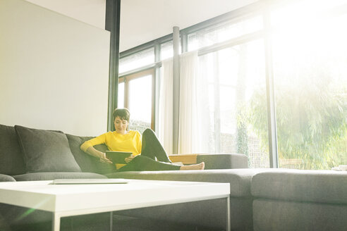 Woman sitting on couch in the living room using digital tablet - SBOF01871