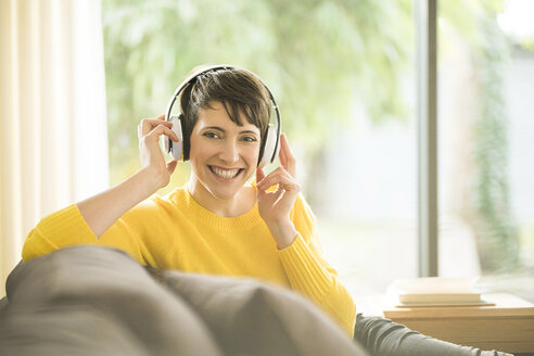Portrait of happy woman sitting on the couch at home listening music with headphones - SBOF01874