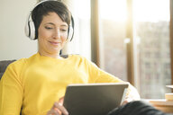 Portrait of happy woman with headphones sitting on the couch at home looking at digital tablet - SBOF01877
