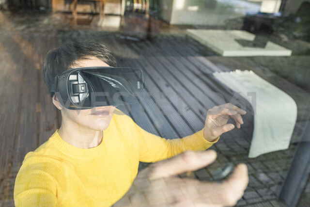 Portrait of woman behind windowpane using Virtual Reality Glasses at home - SBOF01880 - Steve Brookland/Westend61