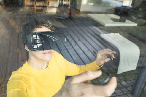 Portrait of woman behind windowpane using Virtual Reality Glasses at home - SBOF01880
