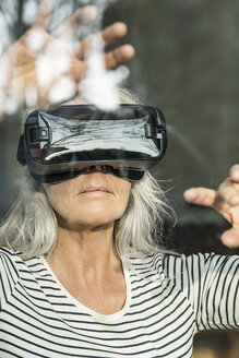 Portrait of mature woman behind windowpane using Virtual Reality Glasses - SBOF01883