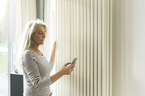 Mature woman with smartphone checking heating in living room of smart home - SBOF01886