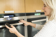 Content mature woman with smartphone checking oven in kitchen of her smart home - SBOF01889