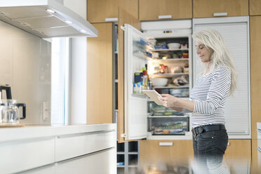 Content mature woman standing in kitchen at smart home checking fridge with digital tablet - SBOF01892