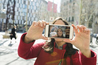Smiling woman taking a selfie in the city - VABF02239