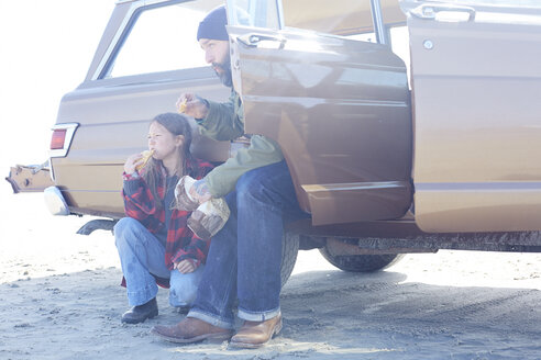 Daughter and father having lunch break on the beach at a car - AMEF00029