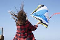 Girl with windswept hair flying kite under blue sky - AMEF00032
