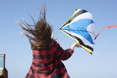 Girl with windswept hair flying kite under blue sky - AMEF00032
