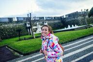 Portugal, Azores Islands, San Miguel, portrait of smiling woman walking through Ponta Delgada - KIJF02410