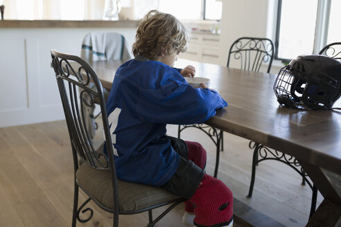 Boy in ice hockey uniform eating cereal table - HEROF26868