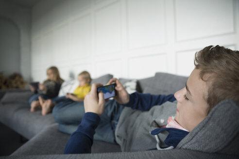Boy playing game on smart phone on sofa - HEROF26901