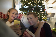 Brother and sister texting near Christmas tree - HEROF26922