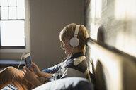 Boy with headphones using digital tablet - HEROF26931