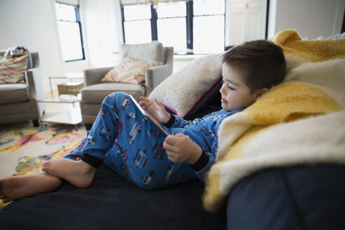 Boy in pajamas using digital tablet on sofa - HEROF26937