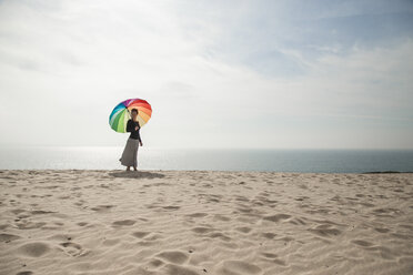 Woman with colorful umbrella walking at the beach - KBF00549